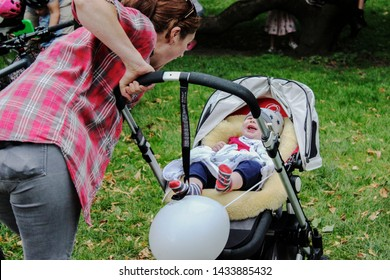 June 2019, Cardiff, Wales. Mother is smiling to newborn in pram/push chair outdoors. cute little baby is laughing because of mum