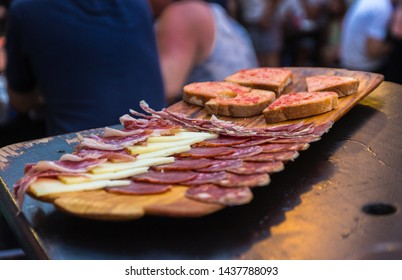 """June 2019. Delicious cold meats and cheeses at La """"casa del Jamon"""" (Calle D Jaime Sanz, 4, Peñíscola, Castellón, Spain). Close up of exquisite fresh spanish food. Toasts served on the side. Summertime"""