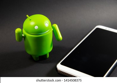 June 2019. Los Angeles,USA. Green plastic Android figure on a black background and with a smartphone. Figure, logo Android, Google
