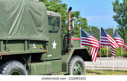 June 22 2018 St Joseph MI USA; a military vehicle is parked behind rows of American flags flying in the wind, at the Lest we forget event in Michigan USA