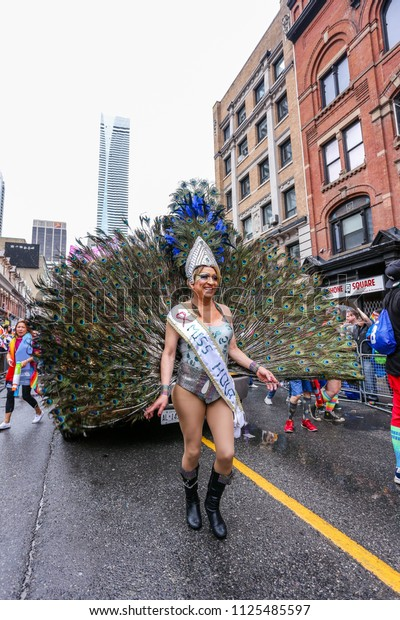 JUNE 24, 2018 - TORONTO, CANADA: PERSON IN PEACOCK OUTFIT WITH GIANT FEATHERS MARCHES AT 2018 TORONTO PRIDE PARADE.
