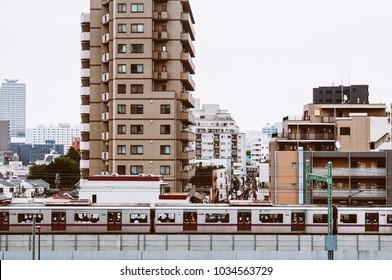 June 25, 2014 Shinagawa, Tokyo, Japan : Shinagawa district scene with residential buildings and commuter train running pass