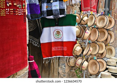 June 25, 2018. Traditional Mexican sombrero straw hats and a Mexican flag poncho for sale in Real de Catorce, San Luis Potosi, Mexico.