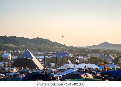 June 25th 2011. Glastonbury Festival. The pyramid stage at Glastonbury Festival with a hot air balloon floating in the background and Glastonbury Tor in the distance. On a sunny evening.