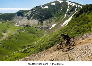 JUNE 26, 2010. MORZINE, FRANCE. A man rides a mountain bike down a steep trail in a purpose built 'bike park' in the French Alps. Snow on the mountain behind.