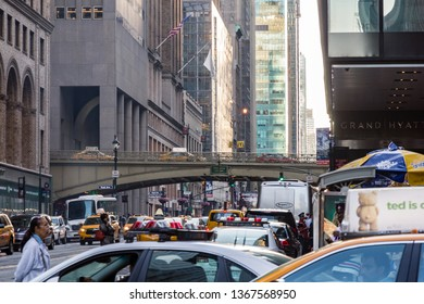 June 26, 2015 - E 42nd Street, New York,  USA. View looking down the bustling and busy street surrounded by towering skyscrapers and with Pershing Square bridge taking taxis into grand central