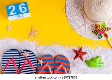 June 26th. Image of june 26 calendar on yellow sandy background with summer beach, traveler outfit and accessories. Summertime concept