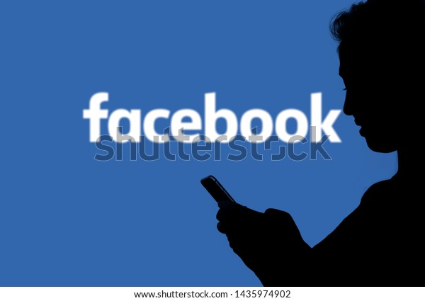 June 27, 2019, Brazil. In this photo illustration silhouette of a person looking at the smartphone with the Facebook logo in the background.