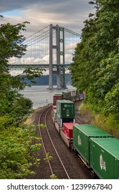 JUNE 28, 2014, TACOMA,WA: An overhead view, looking north, of a Union Pacific Railroad freight train as it rolls down the tracks, with the famous Tacoma Narrows Bridge in the distance.
