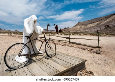 JUNE 29 2015 - Rhyolite, Nevada: Abandoned plaster ghost statue and a bike with wooden miner statues in the distance. Rhyolite is a former mining town, turned ghost town.