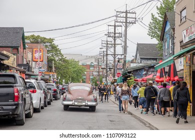 JUNE 3, 2018 - TORONTO, CANADA:  VINTAGE 1950s CAR ON STREET, PEOPLE WALKING BESIDE IT, IN KENSINGTON MARKET.