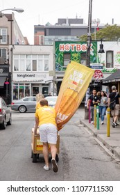 JUNE 3, 2018 - TORONTO, CANADA: PEOPLE PUSH A BUDWEISER PROMOTIONAL CART IN KENSINGTON MARKET.
