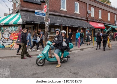 JUNE 3, 2018 - TORONTO, CANADA: TWO PEOPLE ON ELECTRIC SCOOTER IN KENSINGTON MARKET.