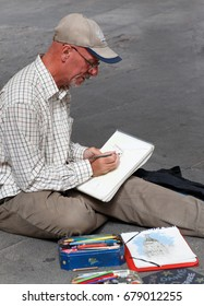 June, 30  2017 Madrid, Spain Street sketcher making a picture from the ground
