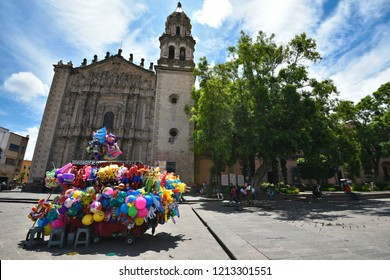 June 30, 2018. San Luis Potosí, Mexico. Panoramic view of Plaza del Carmen with the Baroque style Templo de Nuestra Señora del Carmen and the traditional balloon vendor in the foreground.