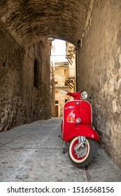 June 30, 2019 - Rome, Lazio, Italy - A red Piaggio Vespa Sprint, parked in an alleyway of an ancient village, in Italy. The scooter symbol of Italian design.