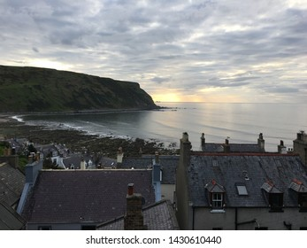 June 3rd 2019: Aberdeenshire, Scotland - the village of Gardenstown rooftops under a stunning overcast sky with the start of a sunset in the distance.