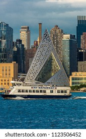 JUNE 6, 2018 - NEW YORK, NEW YORK, USA  - New York City and Hudson River features VIA 57 Building (Sale triangular shaped) and Manhattan Skyline with ferry boat