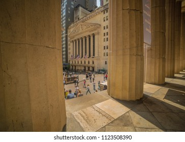 JUNE 7, 2018 - New York, New York, USA - New York Stock Exchange Exerior with US Flags - as seen through columns of Federal Hall