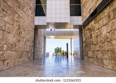June 8, 2018 Los Angeles / CA / USA - Walking corridor between travertine covered walls and below an aerial walkway connecting buildings at the Getty Center;