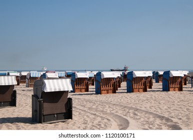 June 8, 2018 - Warnemunde, Germany: Beautiful white sand beach with clear blue sky  with many closed beach chair huts in Warnemunde Germany on this date.