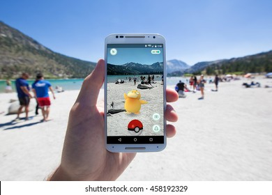 "JUNE LAKE, CALIFORNIA - JULY 24, 2016: The hit augmented reality smartphone app ""Pokemon GO"" shows a Pokemon encounter overlain on a lake shore in the real world."