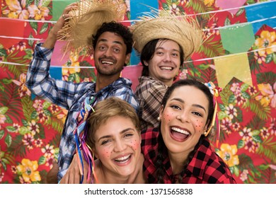 June Party: Festa Junina. Young people in traditional plaid clothes at holiday festival. Decoration of flags in background.