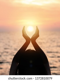 June summer sun solstice concept with silhouette of happy young woman's hands relaxing, meditating and holding sunset against warm golden hour sky on the beach with natural ocean or sea background