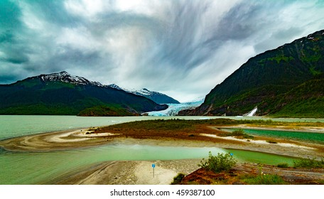 Juneau, AK, USA - May 25, 2016: Mendenhall Glacier in Tongass National Forest.  Clouds  shades in this beautiful spot nearby the Visitor's Center.  View of  glacier, Mendenhall Lake, and Nugget Falls.