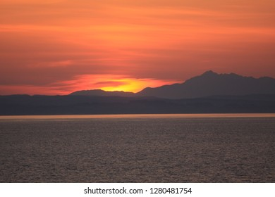JUNEAU, ALASKA : 14 JULY 2009 : A sunset taken from the sea towards the mountains gives an orange and red glow to the sky near to Juneau