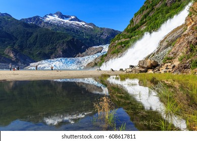 Juneau, Alaska. Mendenhall Glacier Viewpoint with reflection in the lake and waterfall.