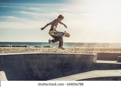 jung skateboarder jumps high and flips his Skateboard / Skatepark Venice Beach California US / in June 2016