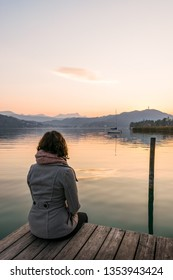 Jung woman sitting alone on a pier at lake wörth and watching the sunrise. Austria, kärnten, klagenfurt, krumpendorf