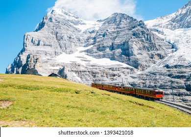 Jungfrau Eigergletscher snowy rocky mountain and red train in Switzerland