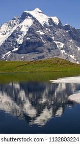 Jungfrau mountain reflected in Grauseewli Lake, canton of Bern, Switzerland, Europe