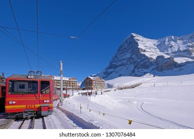 The Jungfrau railway train station at Kleine Scheidegg leading to Jungfraujoch, peak and the famous north face of mount Eiger in the background, Bern, Switzerland, Europe
