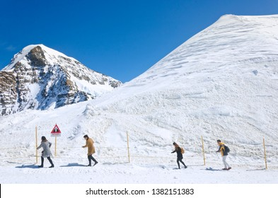 Jungfrau, Switzerland - April 2019 : The tourists on snow trails at the Mt. Jungfrau, Switzerland. Blue sky background.