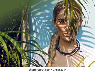 The Jungle Muse .Close up of beautiful fashion model in the jungle scene, thinking while her eager eyes searches for the ray of sun, shadows falling on her face creating a warm lively atmosphere.