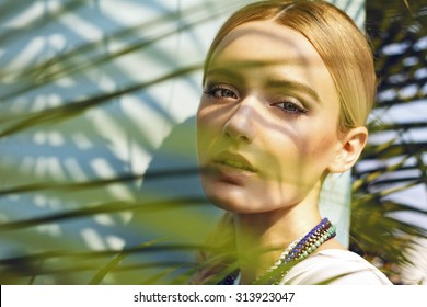 The Jungle Muse. Close up of beautiful fashion model in the jungle scene, thinking while her eager eyes searches for the ray of sun, shadows falling on her face creating a warm lively atmosphere.
