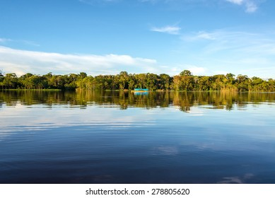 Jungle, sky, and boat reflected in the clear blue water of the Javari River in the Brazilian Amazon Rainforest