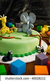 Jungle themed birthday cake with an elephant and giraffe on top, surrounded by building blocks.