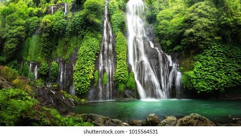 Водопад джунглей каскад в тропическом лесу с скалой и бирюзовым голубым прудом. Его название Banyumala, потому что его двойной водопад в горном склоне