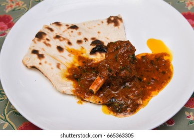 Jungli Laal Maas spicy hot lamb meat curry with roti from Jaipur Rajasthan, India. It is a mutton curry prepared in a sauce of curd and hot spices such as red chillies.
