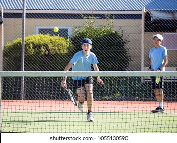 Junior Boy Caucasian Playing Tennis Chasing Ball with Fun Expression