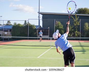 Junior Boy Teenage Children Tennis Player Serving Ball Whilst Playing Match on Court in Summer Weather