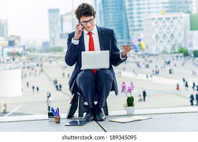 Junior executive dynamic leader phoning outside of his office