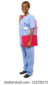Junior female doctor under training. Ready to attend class holding backpack and clipboard