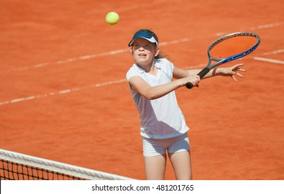 Junior female tennis player attacking with backhand volley