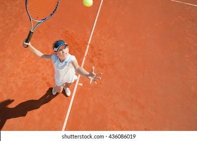 Junior female tennis player on serve.