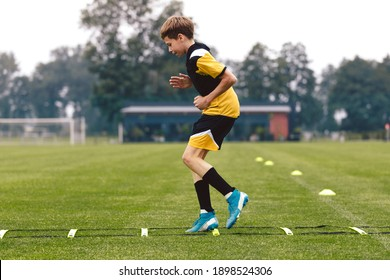 Junior football club player training on soccer ladder. Football training for sport team. Young boy runnong on agility ladder. Football training equipment: ladder, goal and cones